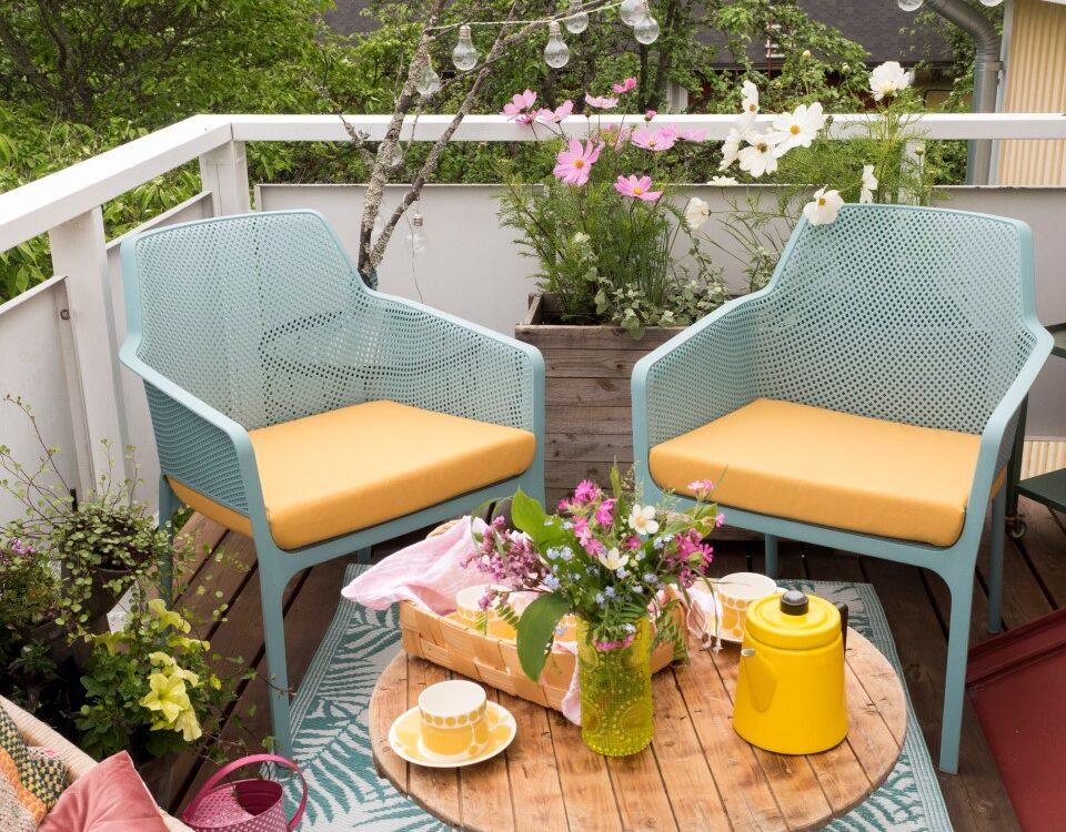 Giitun turkoosit Nardi Net tuolit Keltainen kahvipannu bloggaajan parvekkeella.